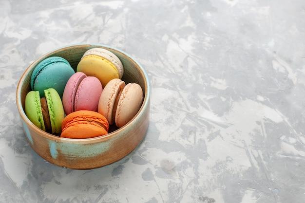 Vista frontale colorati macarons francesi deliziose torte sulla superficie bianca chiara