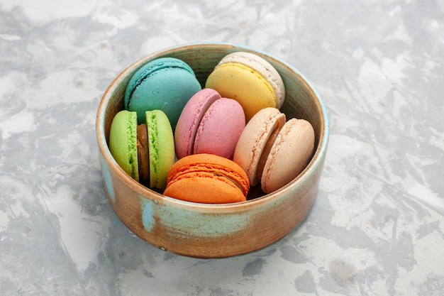 Front view colored french macarons delicious little cakes on white surface