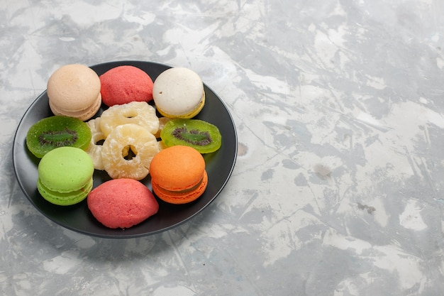 Front view colored little cakes with dried pineapple rings on light-white desk