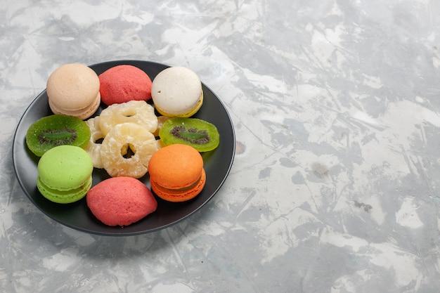 正面図色の小さなケーキとライトホワイトの机の上の乾燥パイナップルリング