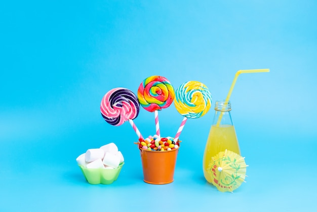 A front view colored lollipops with cocktail and marshmallow spread all over on blue