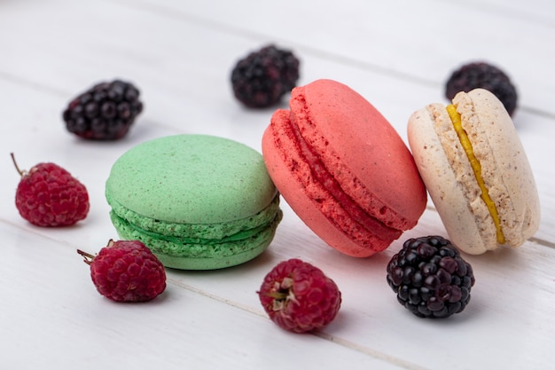Front view of colored macarons with blackberries and raspberries on a white surface