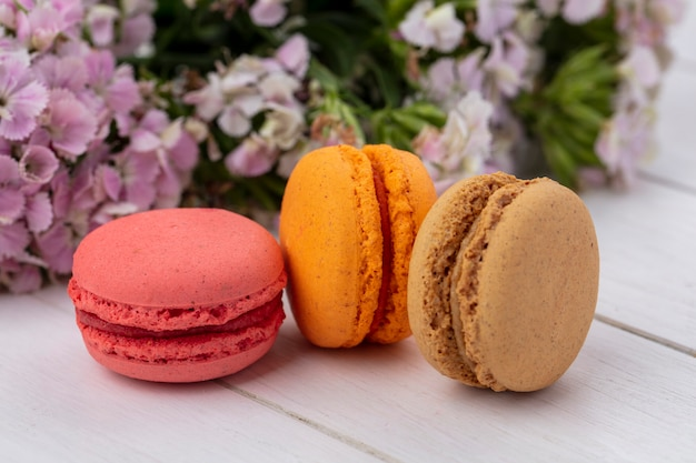 Front view of colored macarons with flowers on a white surface