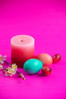 Front view colored painted eggs with candle on pink background holiday spring concept ethnic ornate colourful