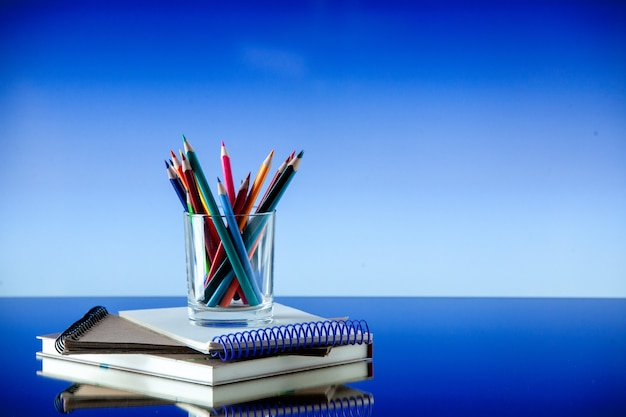 Front view of colored pencils kept in a glass jar on stacked spiral notebooks on the right side on blue color