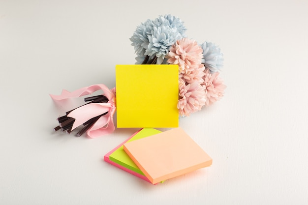 Adesivi colorati vista frontale con fiori su superficie bianca