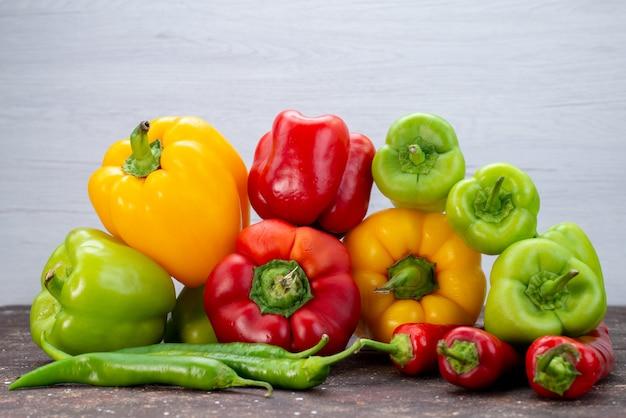Вид спереди красочные болгарские перцы с перцами на коричневом столе овощного цвета