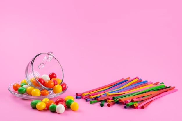 Una vista frontale caramelle colorate insieme a bastoncini di paglia colorati su rosa, caramelle arcobaleno di colore dolce