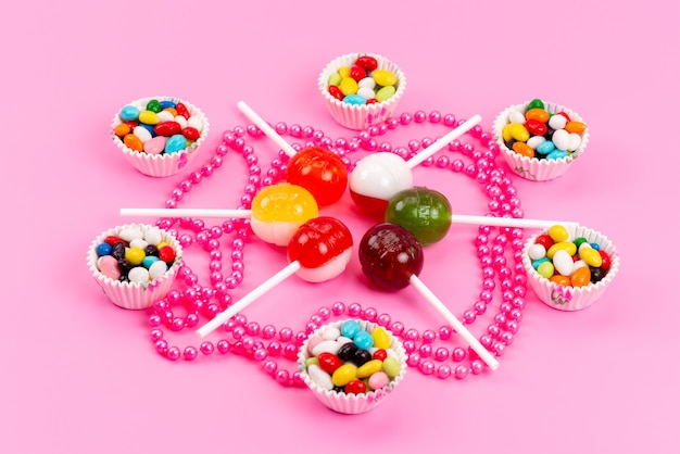 A front view colorful candies along with lollipops isolated on pink, sweet sugar color