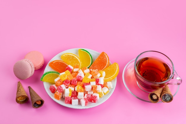 A front view colorful candies and marmalades for the tea time on pink, tea confiture sweet sugar