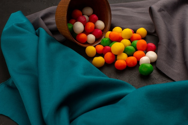 Front view colorful candies sweet inside brown pot on the grey and blue tissue and dark