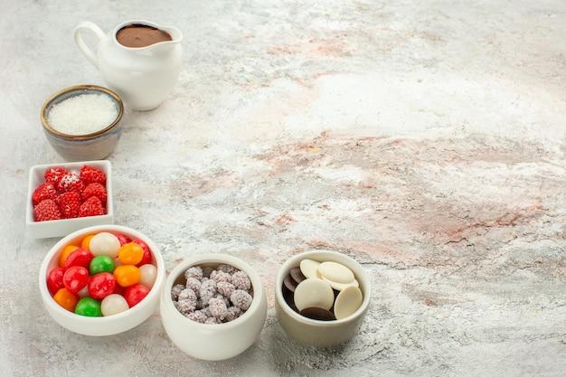 正面図白い背景の上のクッキーとカラフルなキャンディービスケット甘いケーキクッキー 無料写真