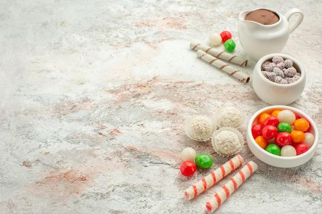 Вид спереди красочные конфеты с печеньем на белом фоне цветной радужный бисквитный чайный торт