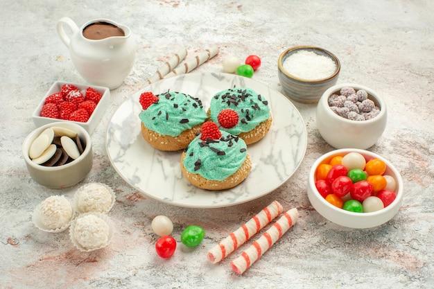正面図白い背景の上のクリーム色のケーキとカラフルなキャンディービスケット甘いケーキクッキー
