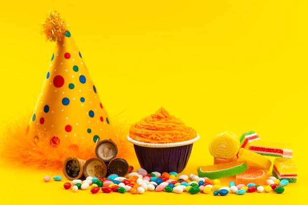 A front view colorful candies with marmalade and birthday cap on yellow, birthday celebration color