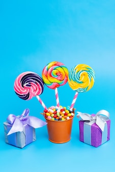 A front view colorful candies with rainbow lollipops and little gift boxes on blue