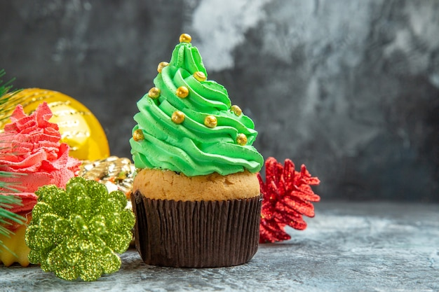 Front view colorful cupcakes xmas ornaments on grey