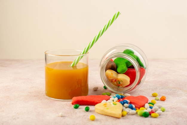 Front view of colorful delicious cookies different formed inside can with candies and fresh peach juice