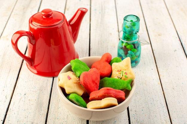 Front view of colorful delicious cookies different formed inside plate with red kettle and candies