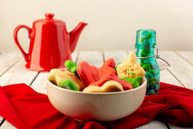 Front view of colorful delicious cookies different formed inside plate with red kettle