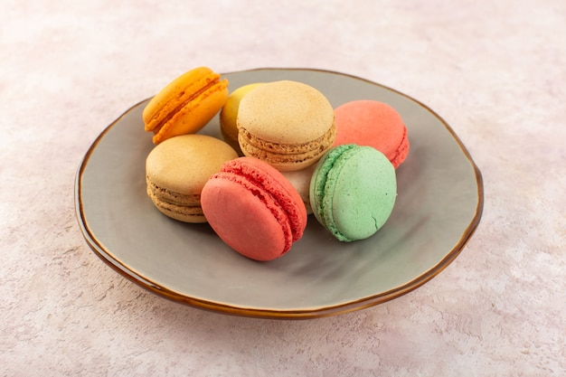 A front view colorful french macarons inside plate on the pink desk biscuit sugar sweet cake