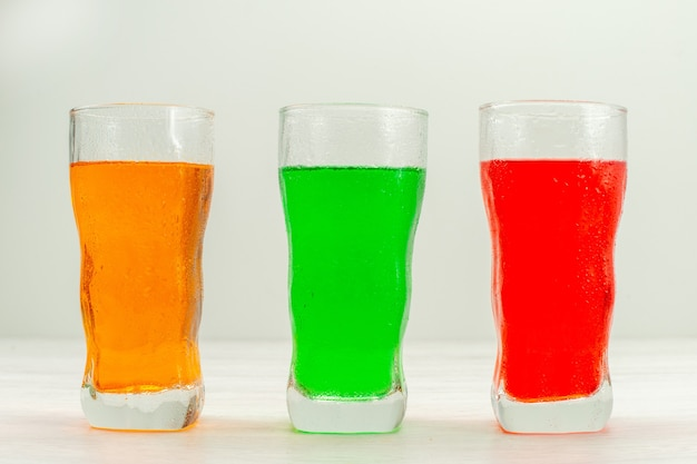 Front view colorful juices inside long glasses on white surface
