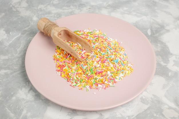 Vista frontale di piccole caramelle colorate all'interno del piatto