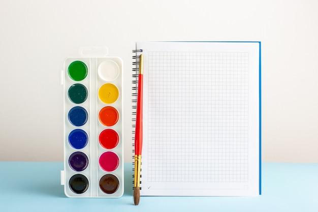 Vernici colorate vista frontale con quaderno sullo scrittorio blu