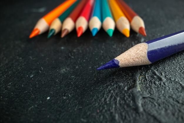 Matite colorate vista frontale allineate sul colore scuro della scuola d'arte con penna da disegno