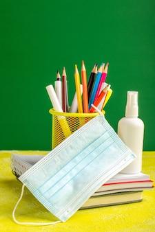 コピーブックと黄色の机の上のスプレーと正面のカラフルな鉛筆