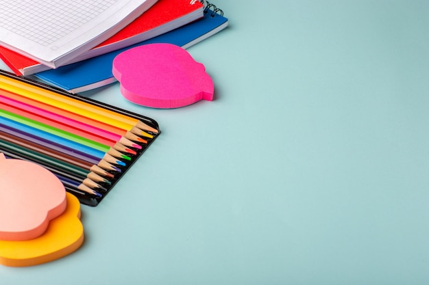 파란색 표면에 카피 북으로 전면보기 다채로운 연필