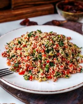 茶色の床に白い皿の中のスライスされた野菜を含む正面のカラフルなサラダ
