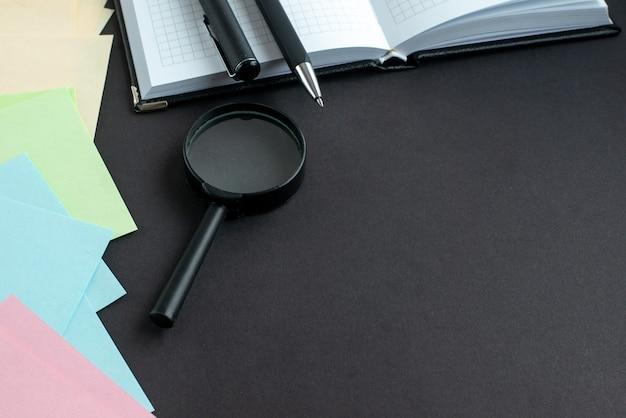 Vista frontale adesivi colorati con penne su sfondo scuro