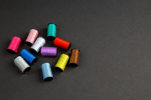 Vista frontale fili colorati sulla superficie scura oscurità vestiti da cucire foto a colori a maglia