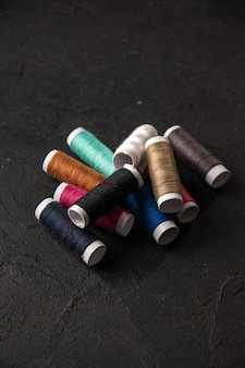 Front view of colorful threads on a dark surface
