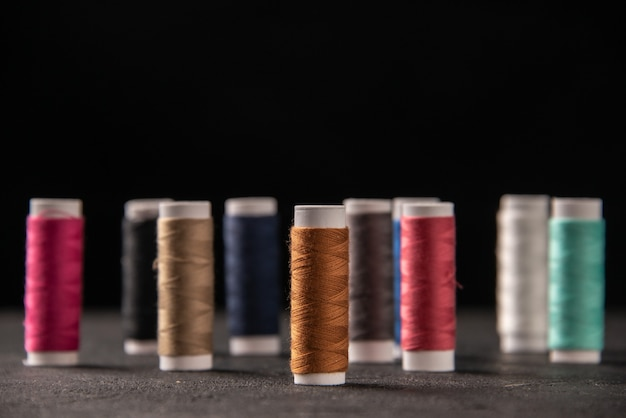 Front view of colorful threads on dark surface