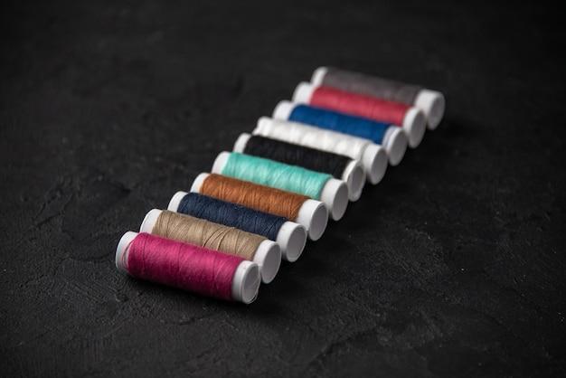 Vista frontale di fili colorati sulla superficie scura