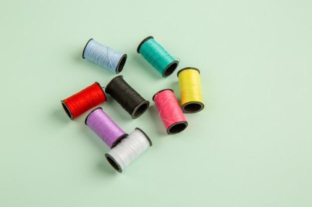 Вид спереди разноцветные нитки на зеленой поверхности шитье одежды цветное фото игла для шитья