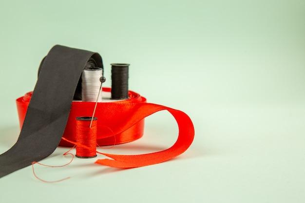 正面図緑の表面に弓でカラフルな糸服は針を縫う写真カラーピン