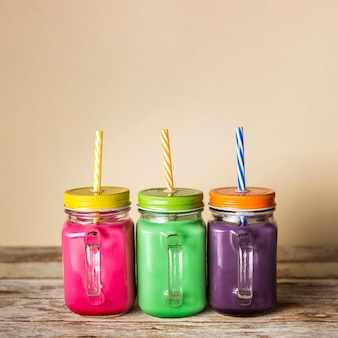 Front view colourful smoothies in jars