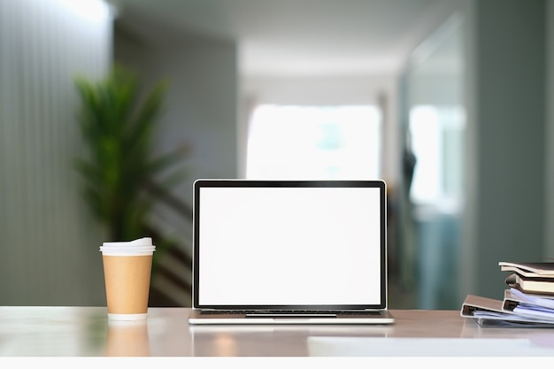 Front view of computer laptop with blank screen, coffee cup and document on white table in living room.