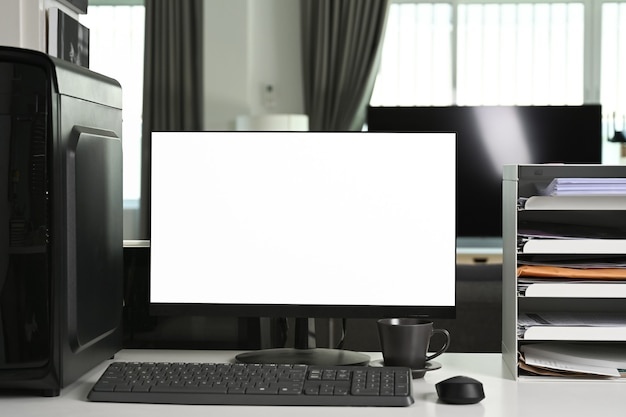 Front view computer with blank screen on white desk in modern home.
