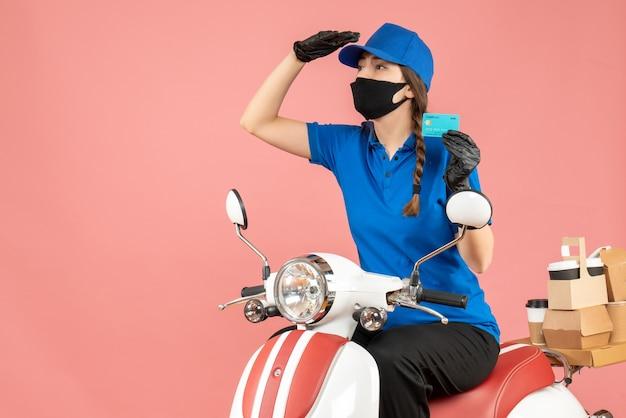 Vista frontale della ragazza del corriere concentrato che indossa maschera medica e guanti seduto su uno scooter con una carta di credito che consegna ordini su sfondo color pesca pastello