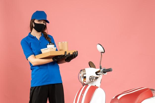 Vista frontale della ragazza del corriere concentrato che indossa guanti per maschera medica in piedi accanto alla moto con in mano piccole torte di caffè su sfondo color pesca pastello