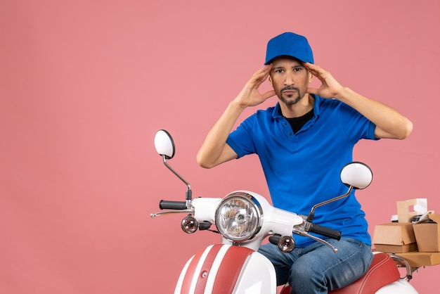 Vista frontale del corriere concentrato che indossa un cappello seduto su uno scooter su sfondo color pesca pastello