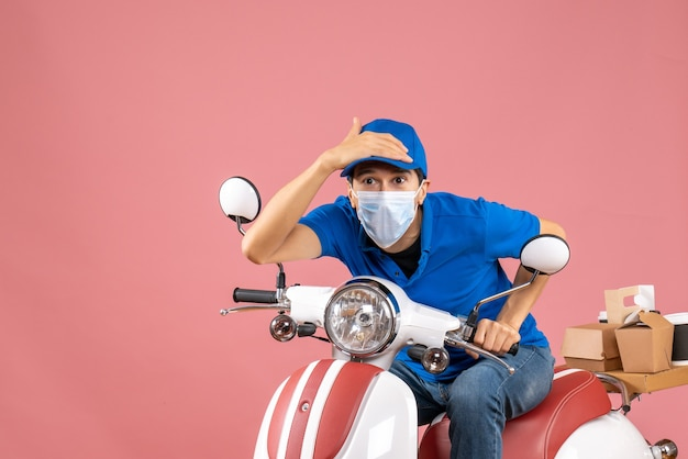 Vista frontale dell'uomo corriere concentrato in maschera medica che indossa cappello seduto su scooter su sfondo pesca pastello