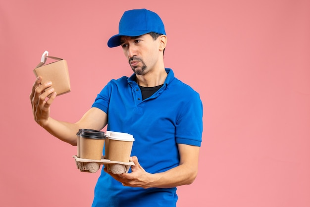 Front view of concentrated emotional male delivery guy wearing hat holding orders