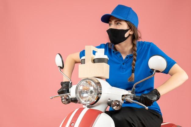 Vista frontale del corriere femminile concentrato che indossa maschera medica nera e guanti che tengono una piccola scatola su sfondo pesca