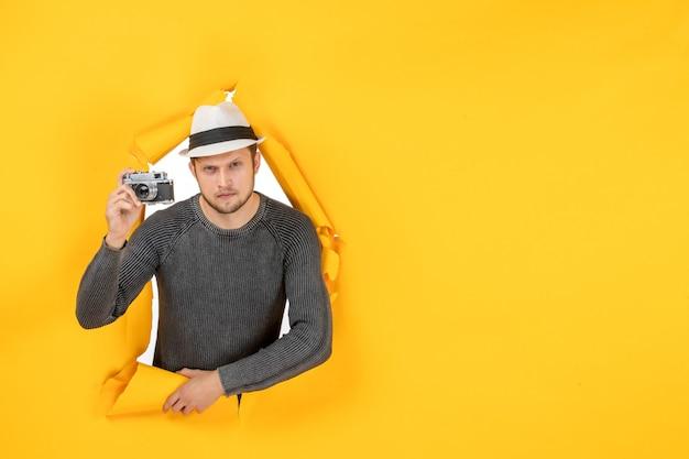 Vista frontale del ragazzo concentrato con un cappello che tiene la macchina fotografica in un muro strappato sul giallo yellow