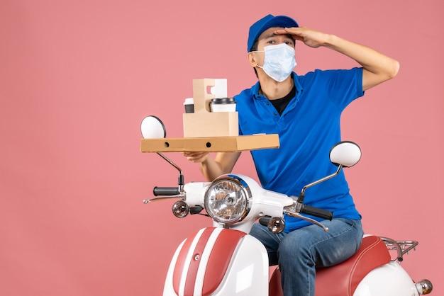 Vista frontale del fattorino maschio concentrato in maschera con cappello seduto su scooter che mostra ordini su sfondo pesca pastello